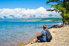 Uma mulher de meia idade aprecia a vista do lago Hovsgol e das montanhas do Sayan oriental mongolia imagens de stock