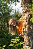 Uma mulher de meia idade branca de riso espreita para fora atrás de uma árvore na floresta imagens de stock