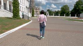 Uma mulher de meia idade em uma camisa cor-de-rosa e em umas caminhadas azuis da calças em torno do local histórico video estoque
