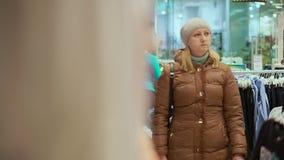 Uma mulher de meia idade em um revestimento do inverno e em um chapéu vai a uma loja de roupa das crianças Cabe a câmera video estoque