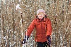 Uma mulher de meia idade na grama seca, no dia de inverno ensolarado imagem de stock