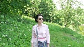 Uma mulher de meia idade nos óculos de sol anda lentamente no parque filme