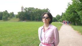 Uma mulher de meia idade nos óculos de sol anda lentamente no parque video estoque