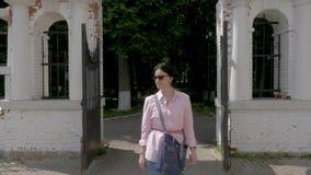 Uma mulher de meia idade nos óculos de sol anda lentamente no parque vídeos de arquivo