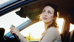 Uma mulher de meia idade pensativa e calma senta-se em um carro Admira a natureza através do estar aberto Noite morna antes do po vídeos de arquivo