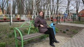 Uma mulher de meia idade que senta-se em um banco video estoque