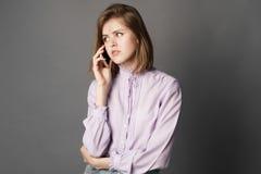 Uma mulher de negócio é estando e de fala em um telefone celular Algo escreve e pensa Fotografia do estúdio Um em um backgro cinz Imagem de Stock Royalty Free