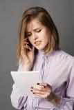 Uma mulher de negócio é estando e de fala em um telefone celular Algo escreve e pensa Fotografia do estúdio Um em um backgro cinz Imagem de Stock