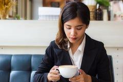 Uma mulher de negócio asiática bonita que senta-se no sofá e que olha o copo do café quente em sua mão imagem de stock