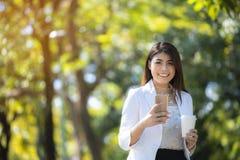 Uma mulher de negócio asiática está relaxando com seus smartphone e coff fotos de stock