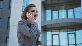 Uma mulher de negócio caucasiano nova bonita que anda fora do prédio de escritórios filme