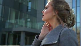 Uma mulher de negócio caucasiano nova bonita que anda fora do prédio de escritórios video estoque