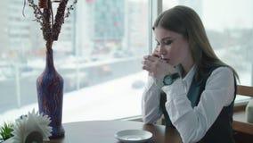 Uma mulher de negócio está sentando-se em um café e está sorrindo-se e está falando-se no telefone filme