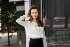 Uma mulher de negócio nova encantador que está na rua em uma camisa branca Imagens de Stock