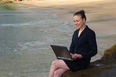 Uma mulher de negócio nova que trabalha em seu portátil na praia Foto de Stock Royalty Free