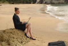 Uma mulher de negócio nova que trabalha em seu portátil na praia Fotografia de Stock Royalty Free