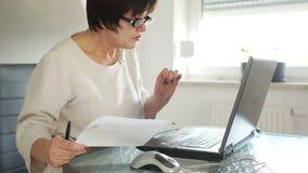 Uma mulher de negócio paga contas usando um computador, pagamentos do Internet, Internet banking Em sua mão guarda uma pena e um  filme