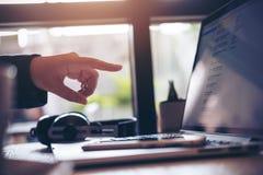 Uma mulher de negócio que aponta seus dedos no portátil no escritório com telefone esperto fotografia de stock