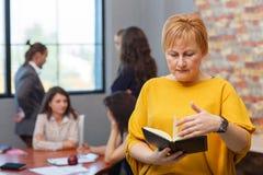 Uma mulher de negócios adulta olha em um caderno No fundo, trabalhadores de escritório imagem de stock royalty free