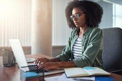 Uma mulher de negócios africana que datilografa no portátil em sua mesa de escritório fotos de stock royalty free