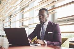 Uma mulher de negócios afro-americano à moda bonita que veste um terno usa seu portátil ao trabalhar foto de stock royalty free