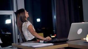 Uma mulher de negócios brincalhão trabalha em um portátil video estoque