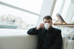 Uma mulher de negócios considerável que senta-se em um café na janela e no café bebendo Ruptura de café no café moderno à moda Imagem de Stock Royalty Free