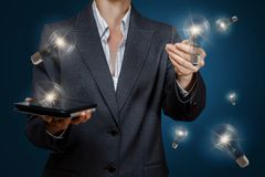 Uma mulher de negócios está operando-se com grupo de ampolas inovativas da ideia fotografia de stock royalty free