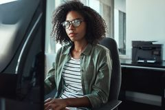 Uma mulher de negócios nova africana que trabalha em sua mesa imagem de stock royalty free