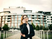 Uma mulher de negócios nova com o smartphone que está na ponte em uma cidade fotografia de stock royalty free