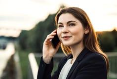 Uma mulher de negócios nova com smartphone fora, fazendo um telefonema foto de stock royalty free