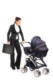 Uma mulher de negócios nova que empurra um carrinho de criança de bebê Fotografia de Stock Royalty Free