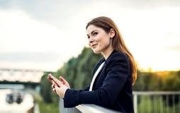 Uma mulher de negócios nova que está no banco de rio, usando o smartphone imagens de stock royalty free