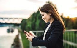 Uma mulher de negócios nova que está no banco de rio, usando o smartphone imagens de stock