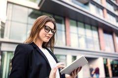 Uma mulher de negócios nova que usa a tabuleta fora na frente de uma construção imagens de stock royalty free