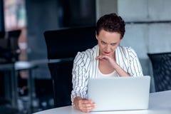 Uma mulher de negócios nova senta-se atrás de seu laptop que olha de sobrancelhas franzidas com sua cabeça em suas mãos devido a  imagem de stock