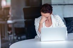 Uma mulher de negócios nova senta-se atrás de seu laptop que olha de sobrancelhas franzidas com sua cabeça em suas mãos devido a  fotos de stock royalty free