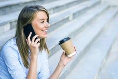 Uma mulher de negócios que verifica o email através do telefone celular e que mantém um copo de café contra a cena urbana Imagens de Stock