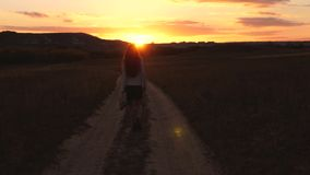 Uma mulher de neg?cio anda ao longo de uma estrada secund?ria com uma tabuleta em sua m?o, o miertsaet do sol entre os p?s das mu vídeos de arquivo