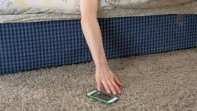 Uma mulher de sono que acorda de uma chamada está arrastando-se atrás do telefone