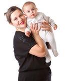 Uma mulher de sorriso é terra arrendada seu bebê nas mãos imagem de stock