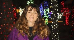 Uma mulher de sorriso bonita com luzes do feriado atrás imagens de stock