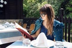 Uma mulher de sorriso em um restaurante com o menu nas mãos imagens de stock