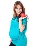 Uma mulher de sorriso grávida está prendendo uma maçã Fotografia de Stock