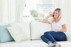 Uma mulher de sorriso que senta-se no sofá como fala em seu telefone Foto de Stock