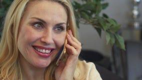 Uma mulher de sorriso tem uma conversa telefônica video estoque