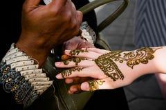 Uma mulher de trabalho que tattooing com hena, jéna ou hena nas mãos de um turista foto de stock