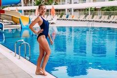 Uma mulher delgada de sorriso nova em um escuro - o roupa de banho azul dos esportes está estando pela associação exterior no hot imagem de stock royalty free