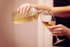 Uma mulher derrama o vinho em um vidro de vinho Fotografia de Stock Royalty Free