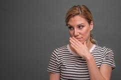 Uma mulher descreve o desprezo da bisbolhetice ou o descontentamento contra um fundo cinzento imagens de stock royalty free